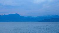 Unscharfe Silhouette der Berge am Gardasee zur Blauen Stunde