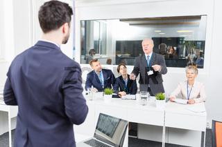 Älterer Geschäftsmann diskutiert mit Redner