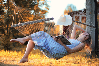 Beautiful girl in hammock reading a book