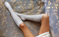 close up of woman legs in winter knee socks in bed