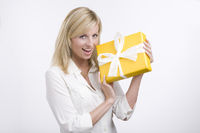 Beautiful business woman holding a gift isolated o