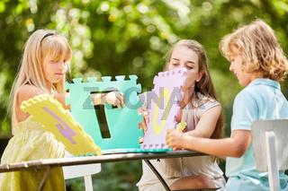 Kinder und Mutter bauen Haus aus Puzzleteilen