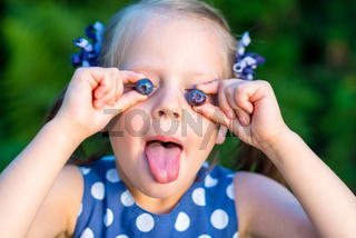 Smiling girl holding blueberries in front of her face - showing her tongue