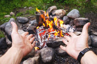 Men's hands are warming around the fire