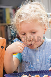 Little girl eating dessert