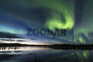 Nordlicht (Auroa borealis) spiegelt sich in einem Waldsee, Lappland