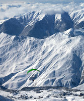 Paragliding at snowy mountains over ski resort