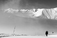 Black and white view on off-piste slope with snowboarder and mountains in mist