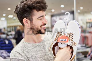 Junger Mann freut sich über Schuhe