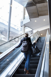 Businesswoman with large black bag and mobile phone ascending on escalator.