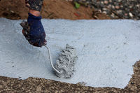 A male painter paints a concrete slope with a paint roller gray paint by an underground pedestrian crossing