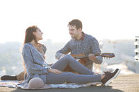 Young man and woman with guitar having fun outdoors