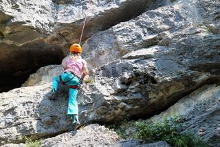 Mädchen klettert an überhängender Felswand