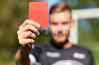 referee hands with red card on football field