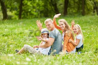 Familie sitzt im Gras und winkt freundlich