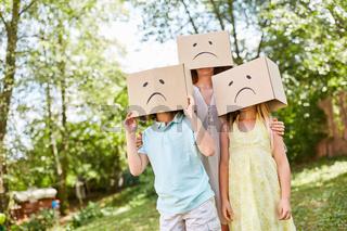 Familie mit Kartons auf dem Kopf schaut traurig