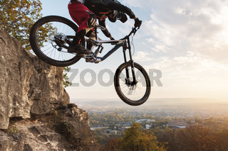 a young rider at the wheel of his mountain bike makes a trick in jumping on the springboard of the downhill mountain path in the autumn forest