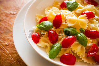 Closeup of Farfalle pasta with cherry tomatoes and basil over a colored background