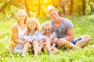 Glückliche Familie sitzt zusammen auf Wiese