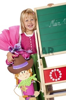 Schulkind mit Schultüte steht am 1. Schultag neben Tafel