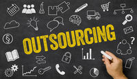 Outsourcing written on a blackboard with icons