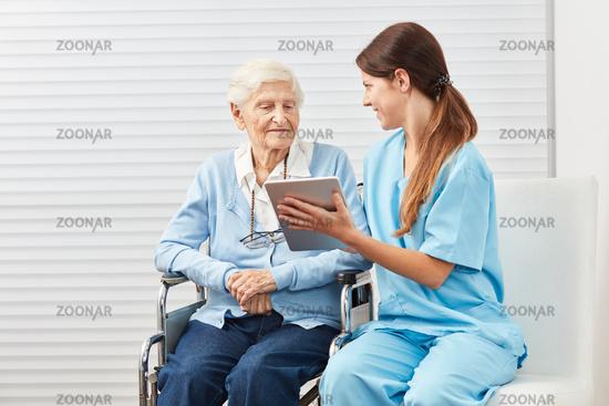 Pflegekraft erklärt einer Seniorin einen Tablet PC