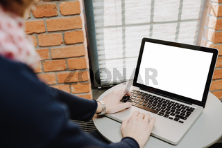 Woman's hands using laptop with blank screen on table