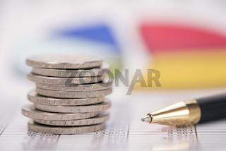 Euromünzen im Stapel vor Bilanz und Börsenkurs