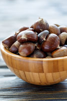 Fresh chestnuts in a wooden bowl.