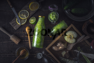 Bottles  and jar with  green smoothie and different ingredients on the wooden tray horizontal