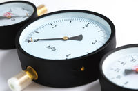 Close-up Pressure sensors in the pipeline - mono-meters. Three monometers of different sizes on a white isolated background in soft focus.