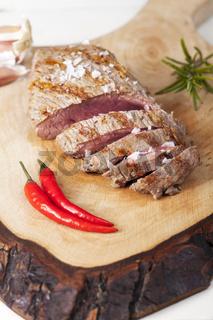 Scheiben eines Steaks auf Holz mit Rosmarin