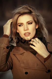 Young fashion blond woman in beige coat walking outdoor