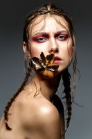 beautiful girl with modern braids and metal flower in mouth