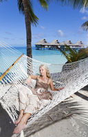 the woman with blonde long hair in  long dress  lies in a hammock on background of the sea