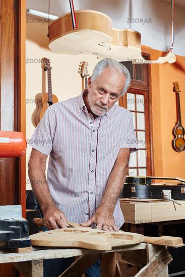 Senior als Gitarrenbauer arbeitet mit Holz