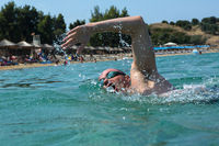 Tourist man in swimming sports glasses is floating in the Aegean Sea on the coast of Sithonia Peninsula