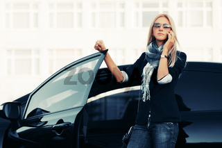 Fashion business woman in sunglasses talking on cell phone beside a her car