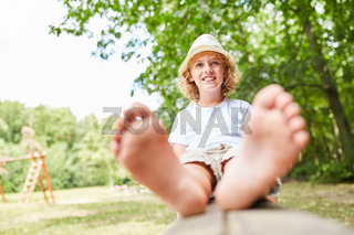 Glücklicher Junge auf einer Parkbank