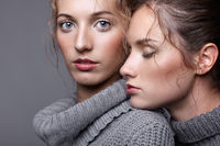 Two young women in gray sweaters on grey background. Beautiful girls stretching hands forward in embrace. One girl with eyes closed