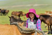 Junge mongolische Frau mit modischem Hut zwischen Pferden