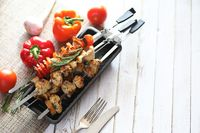Kebab cooked on metal skewers with vegetables