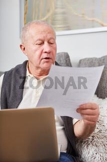 Rentner liest zuhause einen Brief