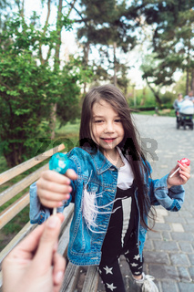Girl sitting on bench with candies