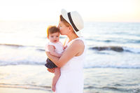 Young beatiful woman with baby on the beach