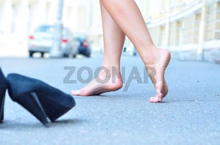 female bare feet dancing on summer street