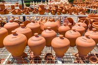 Many orange clay pots outside at pottery