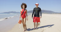 Female and male lifeguards walking along beach