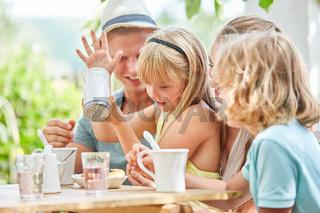 Familie und Mädchen mit Zuckerstreuer