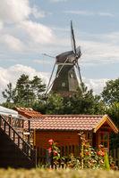 Blick durch einen Garten zur Rysumer Mühle in Ostfriesland